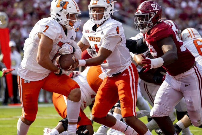 Mercer quarterback Fred Payton (4) hands off to Mercer running back Ethan Dirrim (7) with Alabama defensive lineman Justin Eboigbe (92) already in the backfield during the first half of an NCAA college football game, Saturday, Sept. 11, 2021, in Tuscaloosa, Ala. (AP Photo/Vasha Hunt)