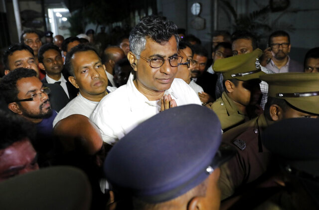 FILE- In this Wednesday, Dec. 18, 2019 file photo, Sri Lankan politician Patali Champika Ranawaka who was the urban development minister before current President Gotabaya Rajapaksa was elected, gestures as prison officers escort him to a magistrate court after his arrest in Colombo, Sri Lanka,. A Sri Lankan court on Tuesday granted bail to the former Cabinet minister who was arrested last week over a years-old traffic accident, a detention the opposition claim is part of a government witch-hunt of political opponents. (AP Photo/Eranga Jayawardena, File)