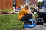 Kristen Bigogno sits on a curb with her belongings and her pets after being evicted from her home Friday, Sept. 17, 2021, in St. Louis. Bigogno is among thousands of Americans facing eviction now that the national moratorium has ended. (AP Photo/Jeff Roberson)
