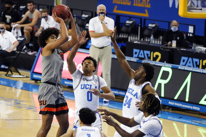 Oregon State guard Ethan Thompson, left, shoots against UCLA during the first half of an NCAA college basketball game Saturday, Jan. 30, 2021, in Los Angeles. (AP Photo/Marcio Jose Sanchez)