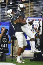 UCF running back Greg McCrae (30) celebrates his touchdown against LSU with wide receiver Gabriel Davis (13) during the first half of the Fiesta Bowl NCAA college football game Tuesday, Jan. 1, 2019, in Glendale, Ariz. (AP Photo/Ross D. Franklin)
