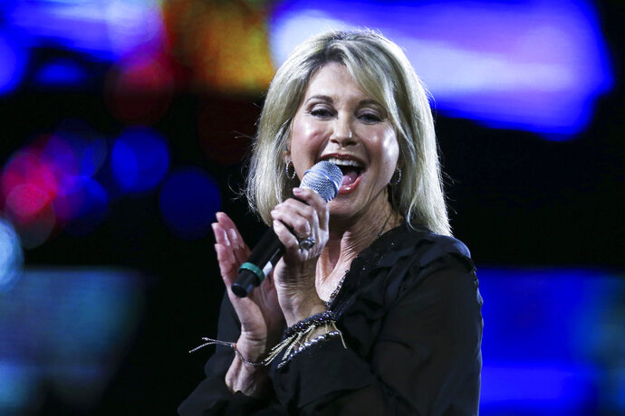 "FILE - In this Feb. 23, 2017, file photo, Olivia Newton-John performs during the Viña del Mar International Song Festival at the Quinta Vergara in Viña del Mar, Chile. Newton-John said she has been diagnosed with cancer for the third time in three decades. The four-time Grammy winner, who will turn 70 on Sept. 26, told Australian news program ""Sunday Night"" doctors found a tumor in her lower back in 2017. (AP Photo/Esteban Felix, File)"