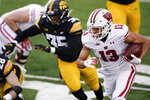Wisconsin wide receiver Chimere Dike (13) runs from Iowa linebacker Barrington Wade (35) during the first half of an NCAA college football game, Saturday, Dec. 12, 2020, in Iowa City, Iowa. (AP Photo/Charlie Neibergall)