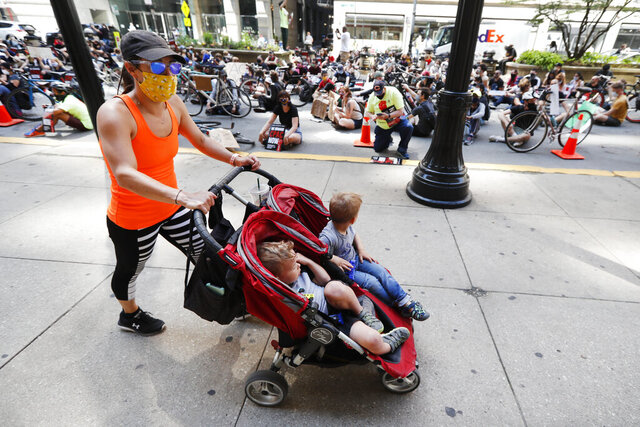A woman and two children pass protesters sitting on La Salle Street in front of Chicago's City Hall, Wednesday, June 17, 2020, demanding that Mayor Lori Lightfoot enact the ordinance for an all-elected Civilian Police Accountability Council, CPAC. (AP Photo/Charles Rex Arbogast)