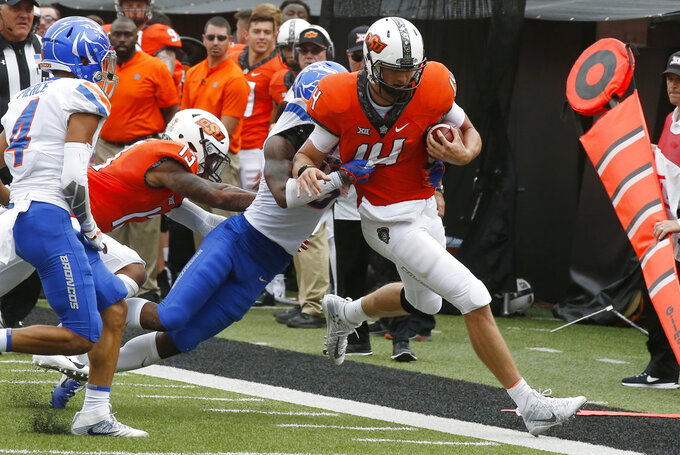 Oklahoma State quarterback Taylor Cornelius (14) is pushed out of bounds by Boise State cornerback Jalen Walker left, in the first half of an NCAA college football game in Stillwater, Okla., Saturday, Sept. 15, 2018. (AP Photo/Sue Ogrocki)