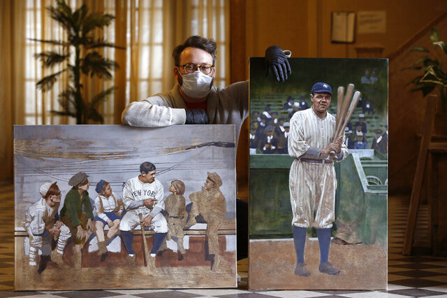 In this Wednesday, April 29, 2020, photo, Brooklyn-based baseball artist Graig Kreindler poses with two of his paintings of Babe Ruth, both unfinished, in the lobby of his residence in New York. Over 200 of Kreindler's paintings form the bulk of the exhibit