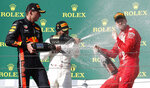 Mercedes driver Lewis Hamilton, center, of Britain, winner of the Hungarian Formula One Grand Prix, celebrates on the podium with second placed Red Bull driver Max Verstappen, left, of the Netherlands, and third placed Ferrari driver Sebastian Vettel, of Germany, at the Hungaroring racetrack in Mogyorod, northeast of Budapest, Hungary, Sunday, Aug. 4, 2019. (AP Photo/Laszlo Balogh)