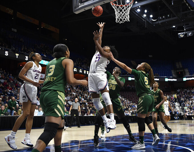 FILE- In this March 8, 2020 file photo, Connecticut's Christyn Williams makes a basket as South Florida's Elena Tsineke, right, defends during the first half of an NCAA college basketball game in at Mohegan Sun Arena in Uncasville, Conn. Final plans were announced Thursday, Nov. 12, 2020, for 11 days of college basketball in November, inside a modified bubble at the Mohegan Sun resort casino. (AP Photo/Jessica Hill, File)