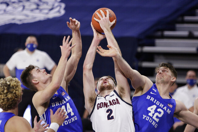 Gonzaga forward Drew Timme (2) grabs a rebound between BYU guard Connor Harding (44) and center Richard Harward (42) during the first half of an NCAA college basketball game in Spokane, Wash., Thursday, Jan. 7, 2021. (AP Photo/Young Kwak)