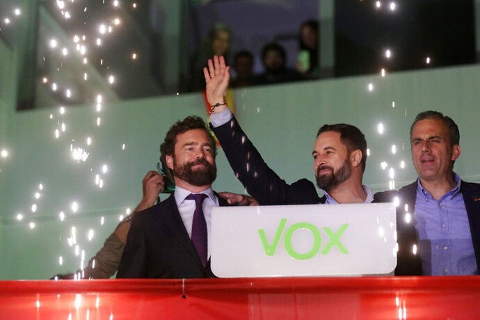 Santiago Abascal, leader of far-right Vox Party, waves to supporters as fireworks go off outside the party headquarters after the announcement of the general election first results, in Madrid, Sunday, Nov. 10, 2019. Celebrating the 52 seats won in the parliament's lower house, more than double than the 24 it received in April, Abascal vowed to use Vox's position as Spain's third political force to hardened policies against illegal immigration, laws against abortion and the crack down on separatists in Catalonia and elsewhere. (AP Photo/Andrea Comas)