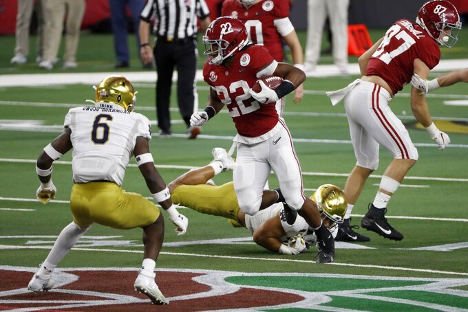Alabama running back Najee Harris (22) attempts to evade a tackle attempt by Notre Dame linebacker Jeremiah Owusu-Koramoah (6) after getting past safety Shaun Crawford, bottom, in the first half of the Rose Bowl NCAA college football game in Arlington, Texas, Friday, Jan. 1, 2021. (AP Photo/Roger Steinman)