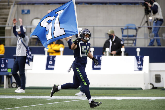 Seattle Seahawks linebacker Cody Barton carries the 12 flag as he runs out of the tunnel before an NFL football game against the New York Giants, Sunday, Dec. 6, 2020, in Seattle. (AP Photo/Larry Maurer)
