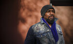 Painter Guy Stanley Philoche, a 43-year-old Haitian immigrant and star in the New York art world, pose outside his East Harlem studio, Thursday Nov. 19, 2020, in New York. After a hugely successful gallery show, Philoche wanted to treat himself to a fancy $15,000 watch, instead he bought the works of fellow artists struggling in the pandemic.