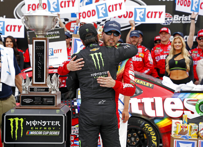 Kyle Busch, facing camera, gets a hug from brother Kurt Busch after winning the NASCAR Cup Series auto race Sunday, April 7, 2019, at Bristol Motor Speedway in Bristol, Tenn. (AP Photo/Wade Payne)