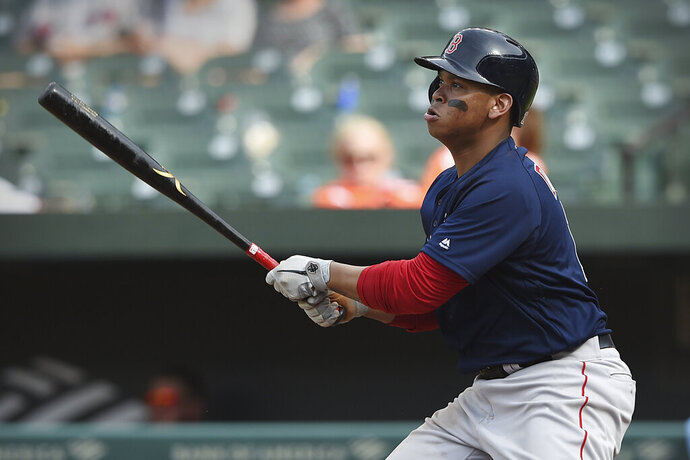 Boston Red Sox's Rafael Devers follows through on a solo home run against the Baltimore Orioles in the 10th inning of a baseball game Sunday, June 16, 2019, in Baltimore. (AP Photo/Gail Burton)