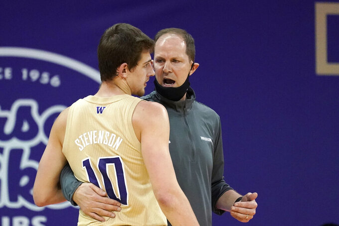 Washington head coach Mike Hopkins, right, has his mask pulled down around his chin as he talks with Erik Stevenson in the first half of an NCAA college basketball game against Washington State, Sunday, Jan. 31, 2021, in Seattle. (AP Photo/Elaine Thompson)
