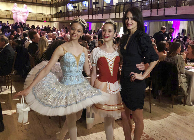 """FILE - Choreographer Melanie Hamrick poses for a photo with young dancers at the gala of Youth America Grand Prix, the world's largest ballet scholarship competition, on April 18, 2019, after the U.S. premiere of her new ballet, """"Porte Rouge"""" (Red Door). Hamrick's Live Arts Global company is producing """"A Night at the Ballet,"""" a free streaming event that premieres this week. The event will treat ballet-starved fans to dancers from America's top companies performing excerpts of classical ballets like """"Romeo and Juliet, """"The Nutcracker"""" and """"Don Quixote.""""  (AP Photo/ Jocelyn Noveck, File)"""