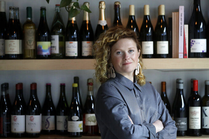 Lauren Friel, owner of Rebel Rebel Wine Bar, in Somerville, Mass., stands for a portrait at the wine bar, Thursday, April 2, 2020. An Associated Press review of the small business aid passed by Congress as part of its coronavirus stimulus package shows that larger companies could quickly claim a disproportionate share of the money, squeezing out many small, locally-based businesses. (AP Photo/Steven Senne)