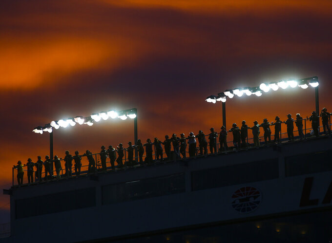 Fans watch the action from a rooftop during a NASCAR Cup Series auto race at the Las Vegas Motor Speedway on Sunday, Sept. 15, 2019. (AP Photo/Chase Stevens)