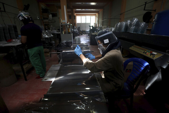 Workers manufacture face masks at a workshop in Bogota, Colombia, Wednesday, April 29, 2020. Oscar Henao a taxi driver by profession and his partner Adan Fajardo, owner of the small packaging workshop, created the plastic protection mask model they called the