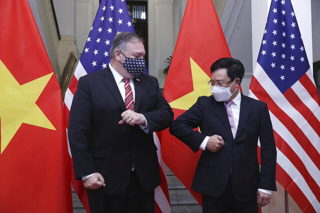 U.S. Secretary of State Mike Pompeo, left, and Vietnamese Foreign Minister Pham Binh Minh gesture with their elbows before a meeting in Hanoi, Vietnam, Friday, Oct. 30, 2020. Pompeo is wrapping up an anti-China tour of Asia in Vietnam as the fierce American presidential election race enters its final stretch. (Bui Lam Khanh/VNA via AP)