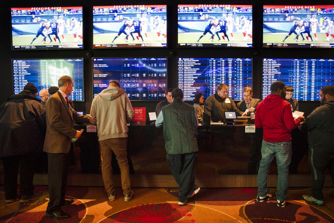 FILE - In this Thursday, Dec. 13, 2018, file photo, gamblers place bets in the temporary sports betting area at the SugarHouse Casino in Philadelphia. About six in 10 Americans want betting on professional sports events to be legal in their state, but fewer feel that way about college athletics, according to a new poll conducted by The Associated Press-NORC Center for Public Affairs Research released Wednesday, March 20, 2019.  The poll finds 42 percent favor legal betting on college sports. (AP Photo/Matt Rourke, File)