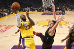 Los Angeles Lakers forward LeBron James, left, shoots as Cleveland Cavaliers forward Kevin Love defends during the first half of an NBA basketball game Monday, Jan. 13, 2020, in Los Angeles. (AP Photo/Mark J. Terrill)