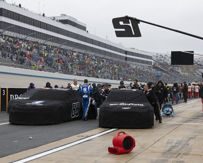 NASCAR teams push their cars down pit road after a NASCAR Cup Series auto race was postponed due to inclement weather conditions Sunday, May 5, 2019, at Dover International Speedway in Dover, Del. (AP Photo/Jason Minto)