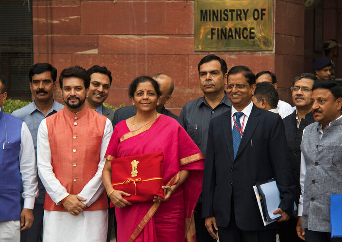 Indian Finance Minister Nirmala Sitharaman, center left, and junior Finance Minister Anurag Thakur, left, stands for the media outside the finance ministry before proceeding towards the parliament house to unveil the annual federal budget in New Delhi, India, Friday, July 5, 2019. India's government says the economy is expected to grow at 7% in 2019-20, up from a five-year low of 6.8% in the past year. (AP Photo/Mariya Amrayeva)