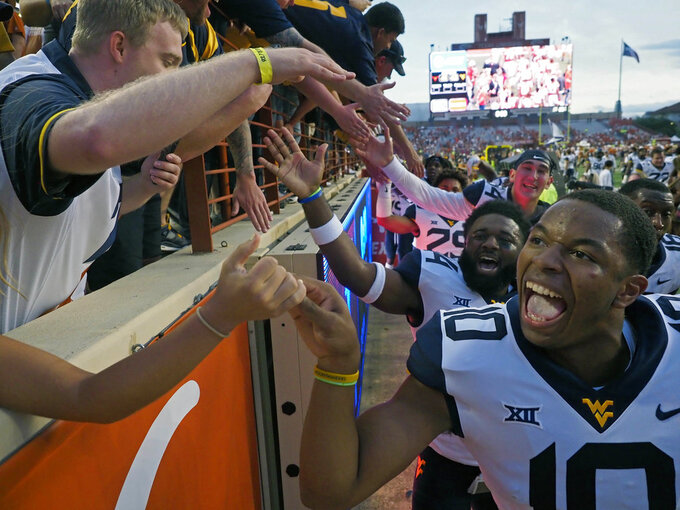 West VirginiaTrey Love, III celebrates with West Virginia fans after defeating Texas in an NCAA college football game, Saturday, Nov. 3, 2018, in Austin, Texas. West Virginia won 42-41. (AP Photo/Michael Thomas)