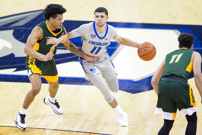 Creighton's Marcus Zegarowski, center, drives the offense against North Dakota State's Dezmond McKinney, left, during the second half of an NCAA college basketball game in Omaha, Neb., Sunday, Nov. 29, 2020. (AP Photo/Kayla Wolf)