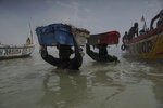 Men wade through the water as they carry the fish cargo from the pirogues to the shore of Bargny beach, some 35 kilometers (22 miles) east of Dakar, Senegal, Thursday April 22, 2021. (AP Photo/Leo Correa)