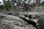 A motorcyle rider negotiates a crack on the road after Taal volcano's recent eruption in Lemery, Batangas province, southern Philippines on Thursday Jan.16, 2020. Taal volcano belched smaller plumes of ash Thursday but shuddered continuously with earthquakes and cracked roads in nearby towns, which were blockaded by police due to fears of a bigger eruption. (AP Photo/Aaron Favila)