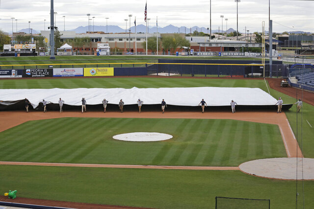 Grounds crew members pull a tarp toward the infield to cover it in anticipation of coming rain after a spring training baseball game between the Los Angeles Angels and the Seattle Mariners Tuesday, March 10, 2020, in Peoria, Ariz. (AP Photo/Elaine Thompson)