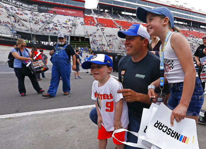 Driver Ryan Newman poses for a photo with 4-year-old Finn Stinnett and 9-year-old Zoie Stinnett from Cleveland, Tenn., before a NASCAR Cup Series auto race, Sunday, April 7, 2019, in Bristol, Tenn. (AP Photo/Wade Payne)