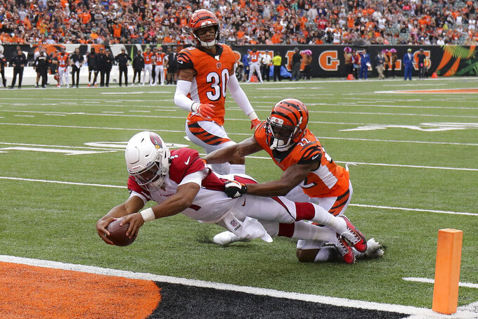 FILE - In this Oct. 6, 2019, file photo, Arizona Cardinals quarterback Kyler Murray (1) leaps in for a touchdown against Cincinnati Bengals cornerback William Jackson (22) in the first half of an NFL football game, in Cincinnati.  Murray went to Arizona with the top pick a year after the Cardinals used a first-rounder on Josh Rosen and has lived up to the billing. Murray has thrown for 2,866 yards while starting every game, has thrown for 14 TDs compared to only six interceptions, and has rushed for 446 yards and four scores. (AP Photo/Gary Landers, File)