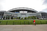 "FILE - In this Aug. 29, 2019, file photo, fans pass by the east side of Mile High Stadium before an NFL preseason football game between the Arizona Cardinals and the Denver Broncos in Denver. The Broncos announced Wednesday, Sept. 4, 2019, that the team will partner with Colorado-based Empower Retirement on a 21-year deal to name the stadium ""Empower Field at Mile High."" (AP Photo/David Zalubowski, File)"