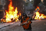 A demonstrator plays a guitar in front of a burning barricade during a protest in Santiago, Chile, Tuesday, Nov. 12, 2019. Students in Chile began protesting nearly a month ago over a subway fare hike. The demonstrations have morphed into a massive protest movement demanding improvements in basic services and benefits, including pensions, health, and education. (AP Photo/Esteban Felix)
