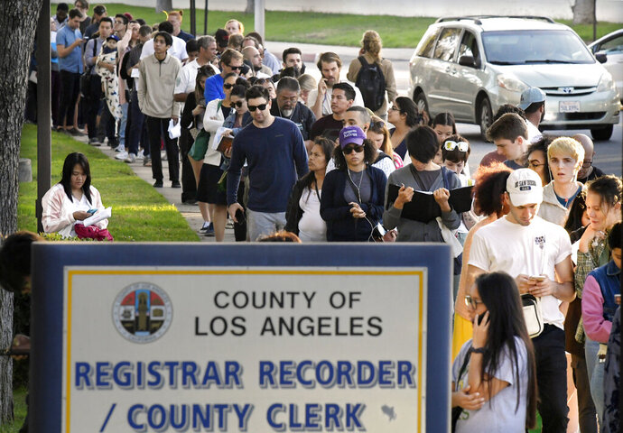 FILE - In this Nov. 6, 2018, file photo, potential voters wait in long lines to register and vote at the Los Angeles County Registrar's office in Los Angeles. California may join many other states in allowing 17-year-olds to vote in primary and special elections, if they will turn 18 before the following general election. The Assembly approved the proposed constitutional amendment on Thursday, Aug. 22, 2019. If two-thirds of senators agree, the measure would go to voters in California's March primary election. (AP Photo/Mark J. Terrill, File)