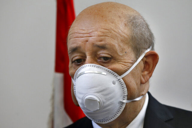 French Foreign Minister Jean-Yves Le Drian wears a mask to help prevent the spread of the coronavirus during his visit to the Carmel Saint Joseph school in the Mechref district, south of the capital Beirut, Lebanon, Friday, July 24, 2020. Le Drian pledged on Friday € 15 million ($ 17 million) in aid to Lebanon's schools, struggling under the weight of the country's major economic crisis. (AP Photo/Bilal Hussein)