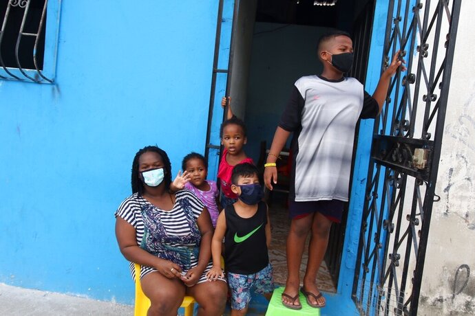 FILE - In this April 14, 2020 file photo, a family waits outside their home to receive food handouts from the local government, in the Cristo del Consuelo neighborhood of Guayaquil, Ecuador. In March and April, Guayaquil was a pandemic hellscape of makeshift morgues, hundreds dying at home, bodies left in the street. But Guayaquil has stabilized since then, sending medical teams and equipment elsewhere in Ecuador and taking in virus patients from outside the city. (AP Photo/Angel de Jesus, File)