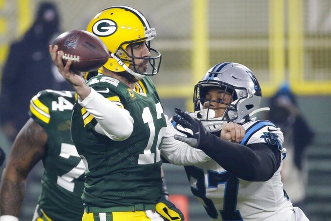 Green Bay Packers' Aaron Rodgers throws while being pressured by Carolina Panthers' Adarius Taylor during the first half of an NFL football game Saturday, Dec. 19, 2020, in Green Bay, Wis. (AP Photo/Mike Roemer)