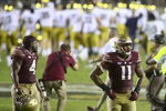 Florida State defensive ends Keir Thomas (4) and Jermaine Johnson II (11) walk off the field dejected as Notre Dame celebrates behind them after an NCAA college football game Sunday, Sept. 5, 2021, in Tallahassee, Fla. Notre Dame won 41-38. (AP Photo/Phil Sears)