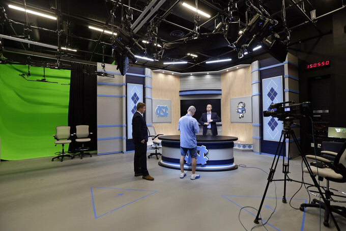 In this photo taken Friday, Aug. 23, 2019, Jones Angell, right, play by play announcer for the North Carolina Tar Heels, prepares for a session in the production studio at the University of North Carolina's ACC Network broadcast facility in Chapel Hill, N.C. The Atlantic Coast Conference finally has its TV channel airing hundreds of league sporting events each year thanks in no small measure to its schools. Administrations around the ACC played a critical role in getting the channel up and running, spending millions to ensure campus broadcast and production facilities were capable of handling telecasts.  (AP Photo/Gerry Broome)