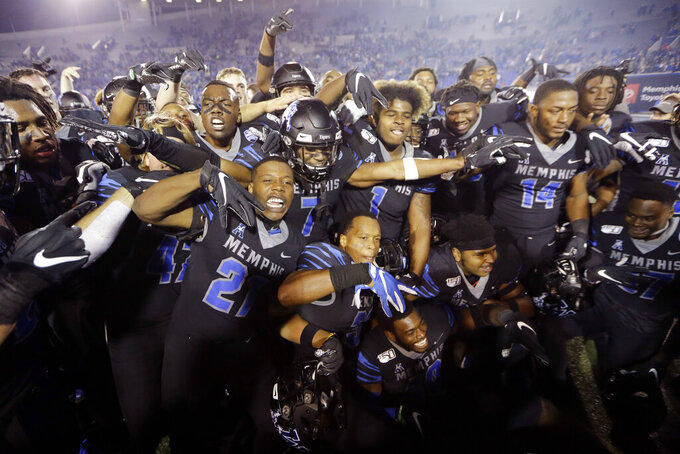 Memphis players celebrate after defeating Cincinnati in an NCAA college football game Friday, Nov. 29, 2019, in Memphis, Tenn. Memphis is to play Cincinnati again next week in Memphis in the conference championship game. (AP Photo/Mark Humphrey)
