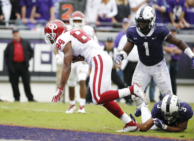 TCU linebacker Jawuan Johnson (1) safety Markell Simmons (3) are unable to stop Oklahoma wide receiver Lee Morris (84) from scoring a touchdown during the first half of an NCAA college football game, Saturday, Oct. 20, 2018, in Fort Worth, Texas. (AP Photo/Brandon Wade)