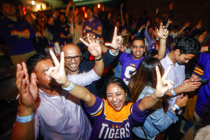 LSU fans celebrate at Varsity Theatre, in Baton Rouge, La., after LSU defeated Clemson 42-25 in the NCAA College Football Playoff championship game, Monday, Jan. 13, 2020. (AP Photo/Brett Duke)