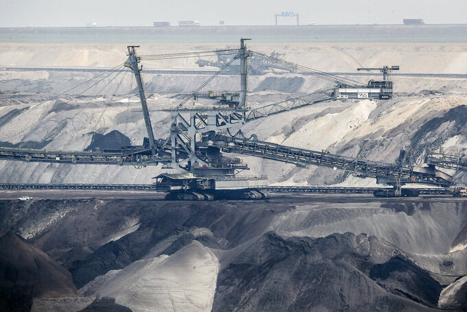 FILE - In this Thursday, April 29, 2021 file photo, giant bucket-wheel excavators extract coal at the controversial Garzweiler surface coal mine near Jackerath, west Germany. A report by the International Energy Agency on Tuesday, May 18, 2021 says immediate action is needed to reshape the world's energy sector in order to meet ambitious climate goals by 2050. This includes ending investments in new coal mines, oil and gas wells. (AP Photo/Martin Meissner, File)