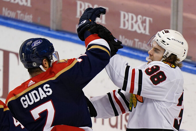 Florida Panthers defenseman Radko Gudas (7) and Chicago Blackhawks left wing Brandon Hagel (38) scuffle during the third period of an NHL hockey game, Saturday, March 13, 2021, in Sunrise, Fla. (AP Photo/Wilfredo Lee)