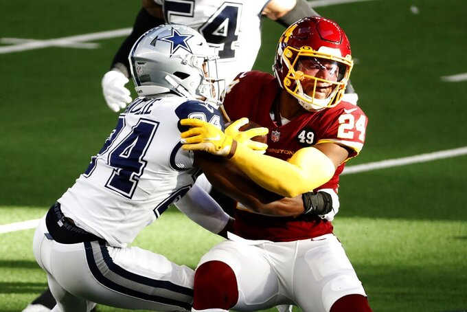 Washington Football Team running back Antonio Gibson (24) is stopped on a carry by Dallas Cowboys cornerback Chidobe Awuzie, left, in the first half of an NFL football game in Arlington, Texas, Thursday, Nov. 26, 2020. (AP Photo/Roger Steinman)